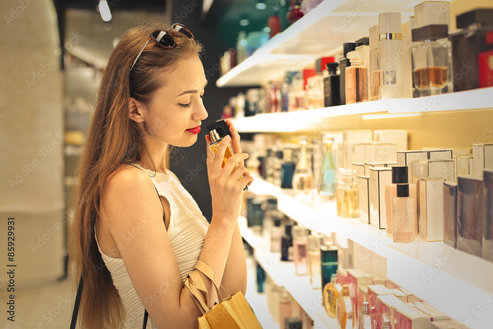 Fototapety, obrazy: Classy woman choosing a perfume inside a perfumery