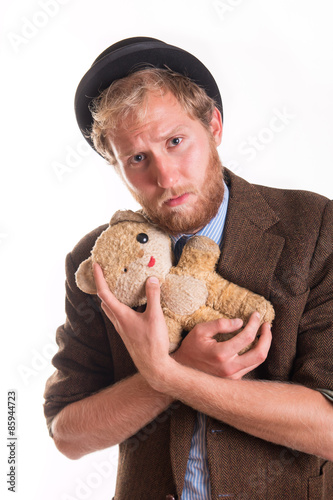 Valokuva  Unhappy old-fashioned man hugs an old teddy bea