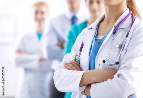 Attractive female doctor in front of medical group Poster