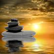 Zen spa concept background - Zen massage stones at sunset reflected in water