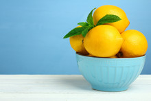 Lemons In A Blue Bowl On A Wooden Background