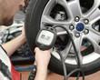 Kontrolle des Reifenluftdrucks durch Mechaniker in einer Autowerkstatt // Check tire air pressure by a mechanic in an auto repair shop