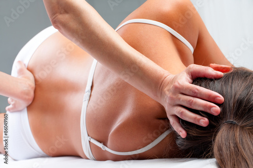 Osteopath doing cranial sacral exercise on woman. Canvas Print