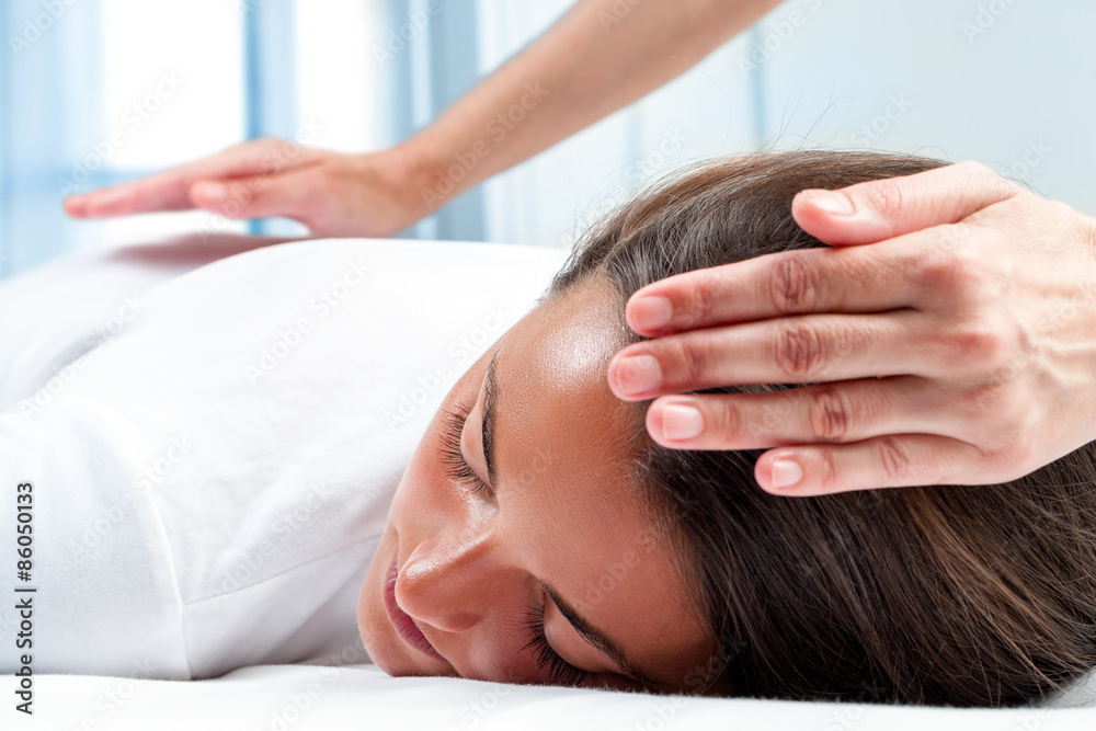 Photo  Therapists hands doing reiki therapy on girl.