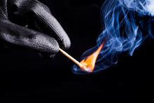 Close-up Of Hand With Match Flame