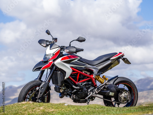 Fotografie, Obraz  A supermotard type motorcycle with cloud in its background