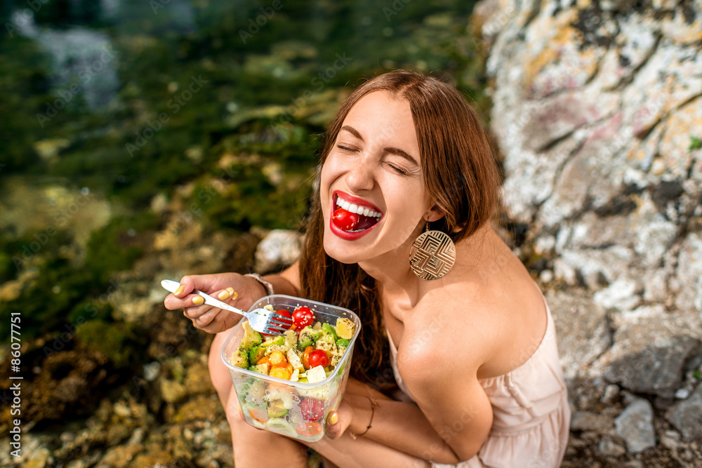 Fototapeta Woman eating healthy salad near the river
