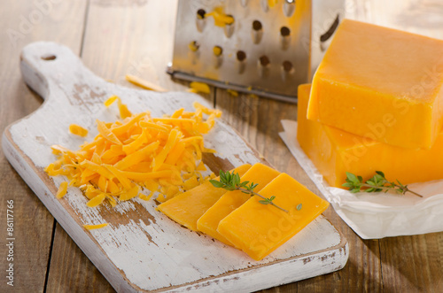 Grated Cheddar Cheese on  a wooden Board.