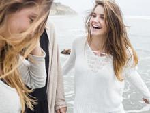 Three Smiling Young Women Walk...