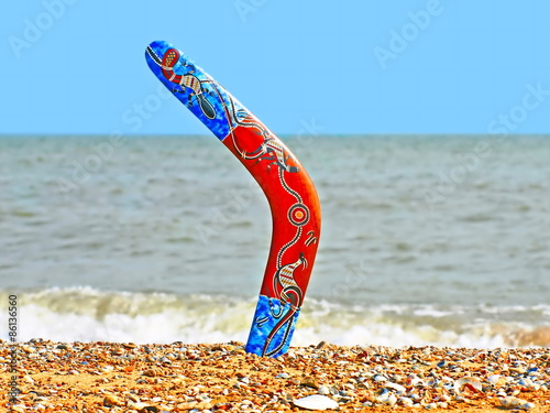 Colorful boomerang on sandy beach against of sea surf. Canvas Print