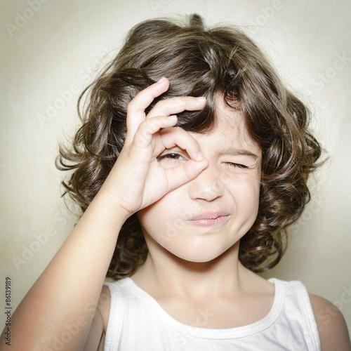 Fotografie, Obraz  Niña mirando a través de un círculo formado con sus manos