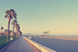 Long sandy beach with palm-lined promenade at sunset. Filtered image in faded, washed-out, retro style; summer travel vintage concept.
