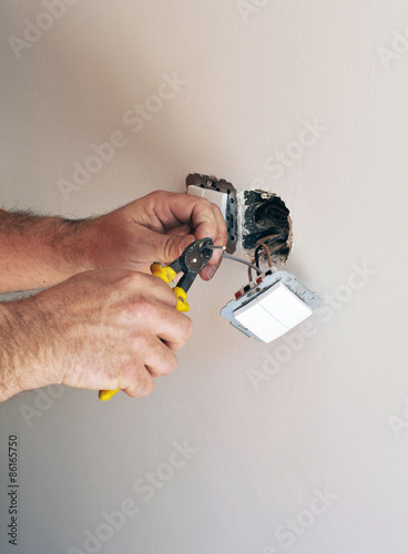 An electrician installing electrical switches during the reform of a house Canvas Print