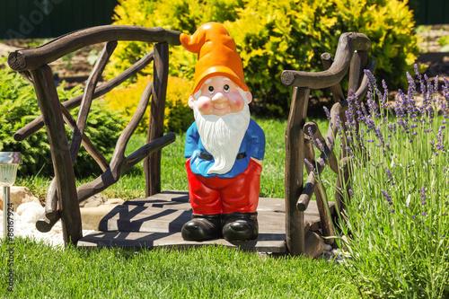 Fotografie, Obraz  Dřevěné dekorační most se zahradním trpaslíkem v domácí zahradě.