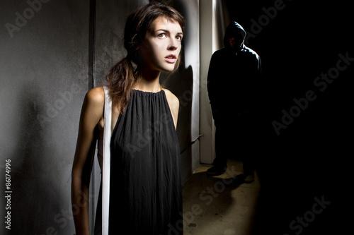 Photo  criminal stalking a woman alone in a dark street alley
