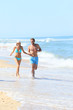 Couple having fun running on the beach