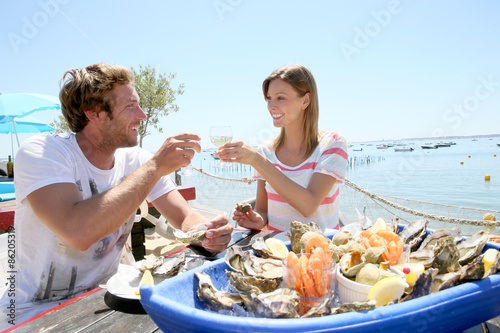 Photo sur Aluminium Coquillage Couple in seafood restaurant tasting fresh oysters