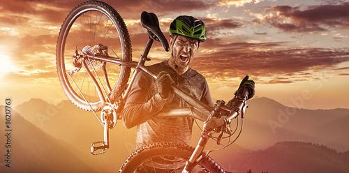 Mountainbiker mit dem Fahrrad auf den Schultern Fototapete