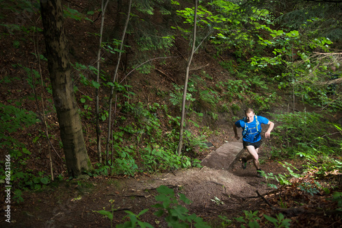 fototapeta na szkło Pojedynczy człowiek działa pod górę na szlak w lesie