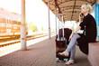Frau wartet auf einem Bahnsteig und telefoniert