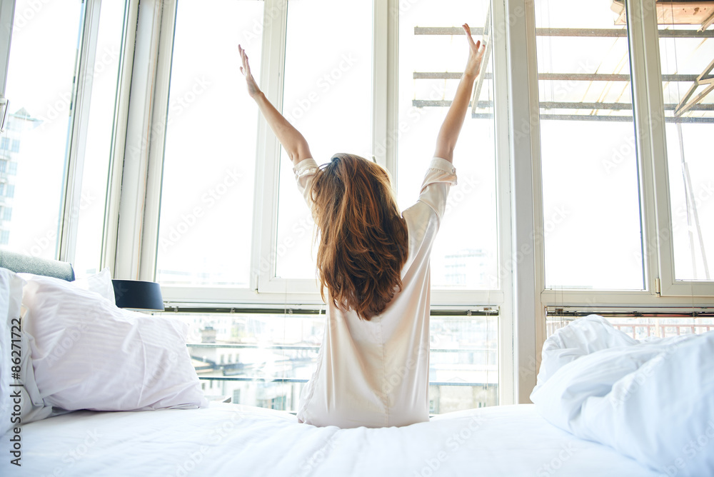 Fototapety, obrazy: Woman stretching in bed, back view