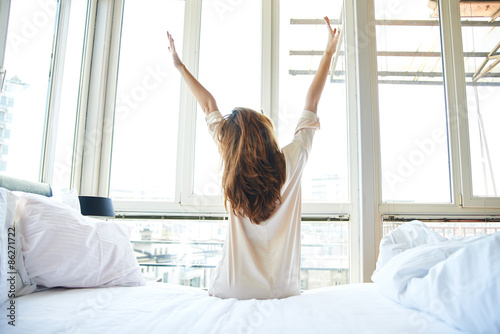 Obraz Woman stretching in bed, back view - fototapety do salonu