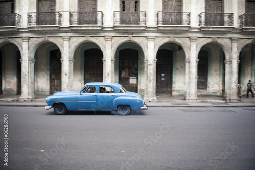In de dag Havana Old American car drives in front of the traditional architecture of a colonial arcade