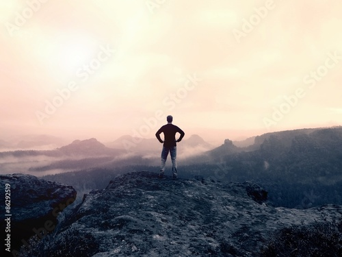 Recess Fitting Beige Man in shirt and jeans on the peak of sandstone rock watching into the misty and foggy valley. Beautiful moment, miracle of nature.