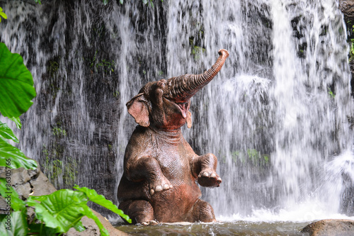 Fotobehang Watervallen Elephant is bathing at the waterfall