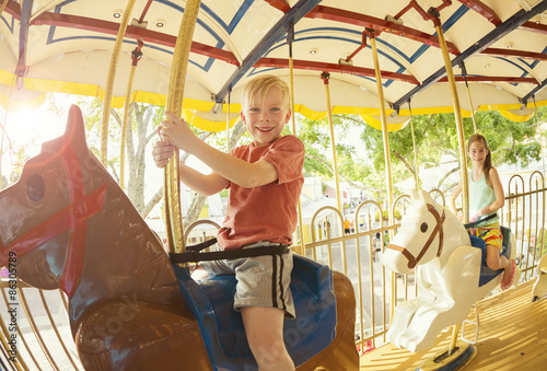 Papiers peints Attraction parc Two cute kids having fun while riding a carousel at an amusement park or carnival