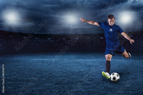Professional soccer or football player during game in full floodlit stadium at night