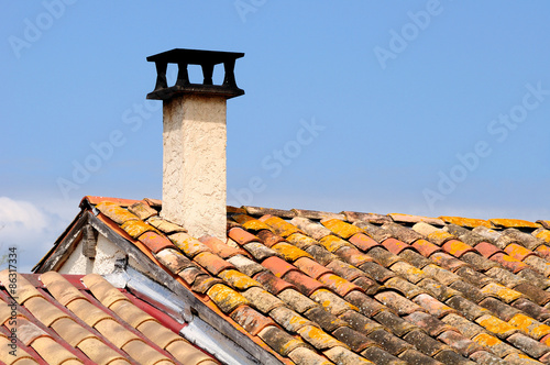 Papiers peints Vin Stone chimney on the roof of a french house.