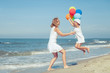 Mother and daughter playing with balloons on the beach at the da