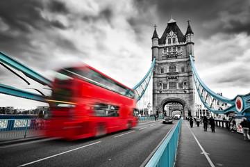 Fototapeta na wymiar Red bus in motion on Tower Bridge in London, the UK