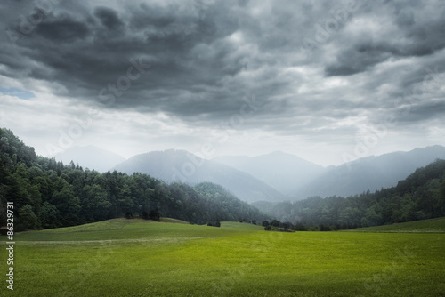 Spoed Foto op Canvas Donkergrijs green meadow and cloudy sky