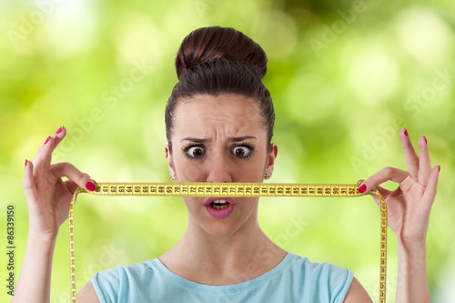 Fotografía  expression girl with tape measure concept of losing weight