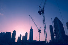 Sunset Skyline Of Construction Cranes Amongst Office Tower Skyscrapers In The Middle East Center Of Trade, Dubai