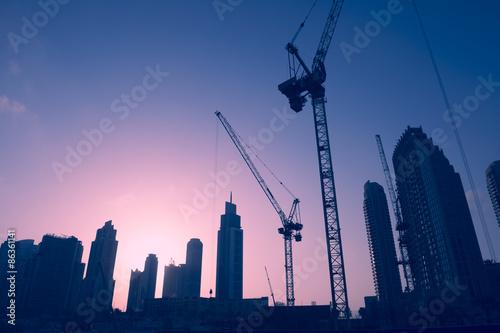 Fototapeta premium Panoramę słońca żurawi budowlanych wśród wieżowców biurowych w centrum handlu na Bliskim Wschodzie w Dubaju