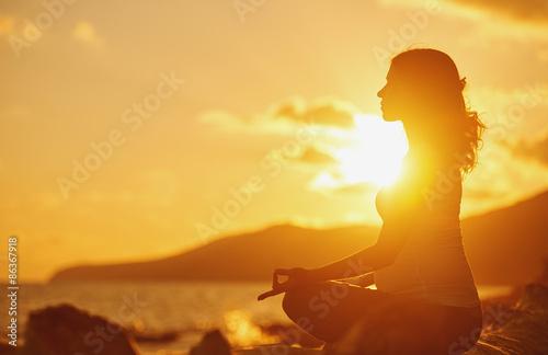 Fotografia  Pregnant woman practicing yoga in lotus position on beach at sun