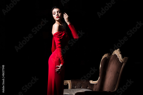 Fotografie, Obraz  Elegant woman in red dress in darkness. Female in dramatic