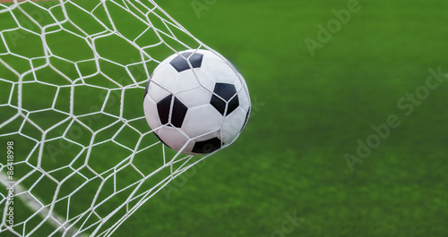 Photo  soccer ball in goal with green backgroung