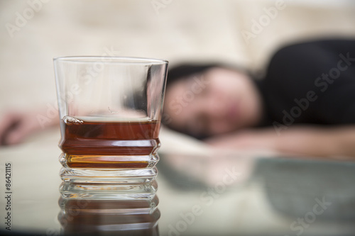 Poster Bar Lonely girl lying drunk close to glass alcohol