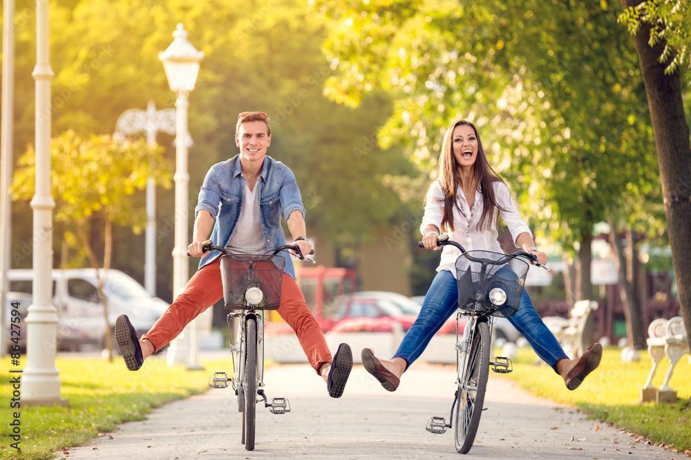 Fototapeta Happy funny couple riding on bicycle