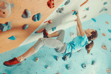 Young woman training in climbing gym