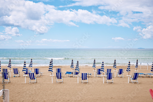 A beach with umbrellas and sun beds on coast Tablou Canvas