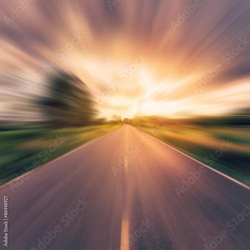 obraz PCV Archiwalne zdjęcie z kraju drogi asfaltowej w motion blur na zachodzie słońca.