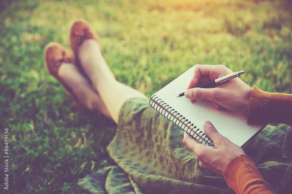 Fototapeta female hands with pen writing on notebook on grass outside
