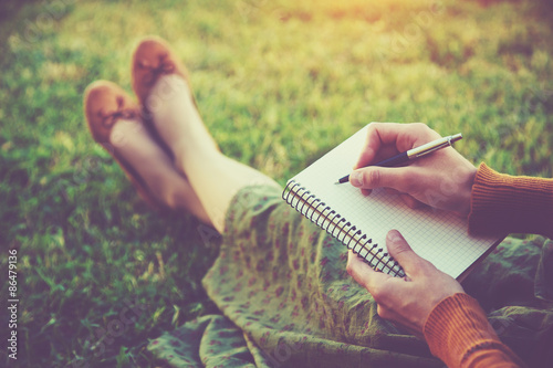 Foto  female hands with pen writing on notebook on grass outside