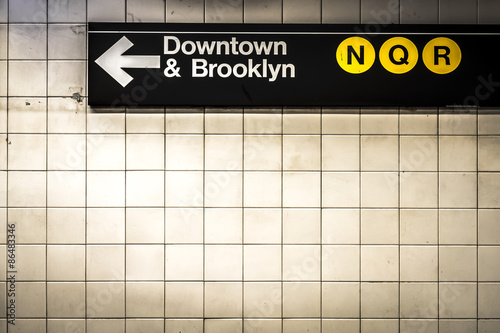Subway sign in Manhattan directing passengers  and travelers to the downtown and Brooklyn trains