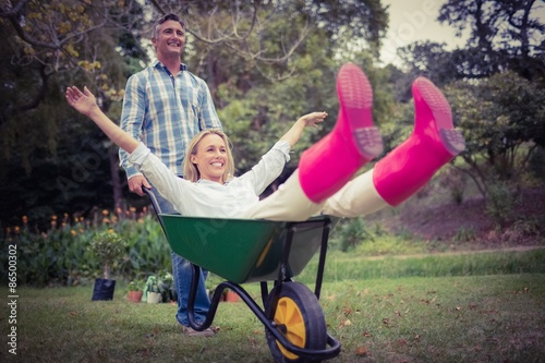Photographie Happy couple playing with a wheelbarrow